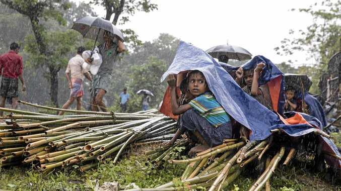 Rohingya children shelter under tarpaulin as heavy rain falls at Kutupalong refugee camp.