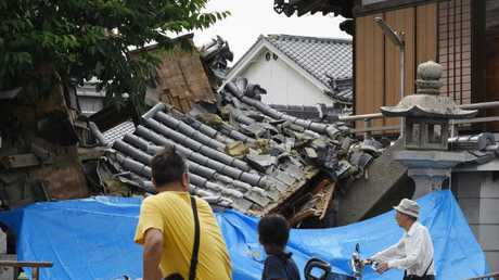 People pause to look at a collapsed house following an earthquake in Ibaraki City, north of Osaka. Picture: AFP/JIJI PRESS/STR
