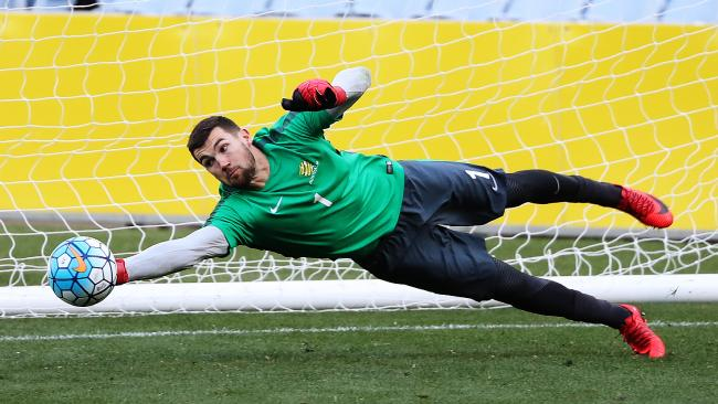 Mat Ryan dives during training. Picture: Brett Costello