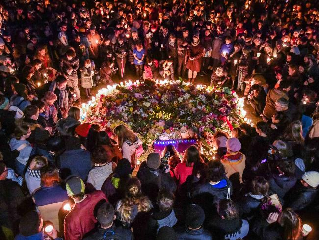 One heartbreaking image being shared on social media has captured the strength in solidarity as the group huddles around the makeshift memorial. Picture: Jason Edwards