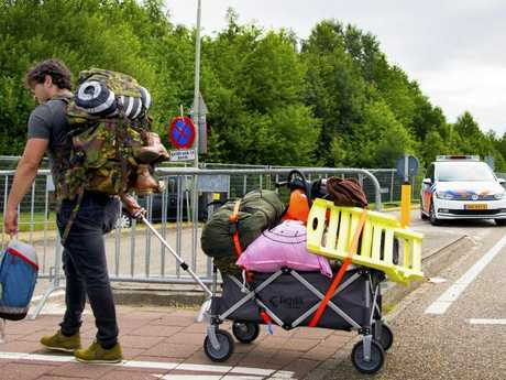 A man walks past police cars near the site of the Pinkpop festival where a van ploughed into festival-goers. Picture: AFP
