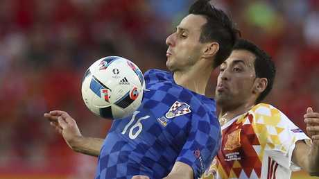 Croatia's Nikola Kalinic is challenged by Spain's Sergio Busquets.