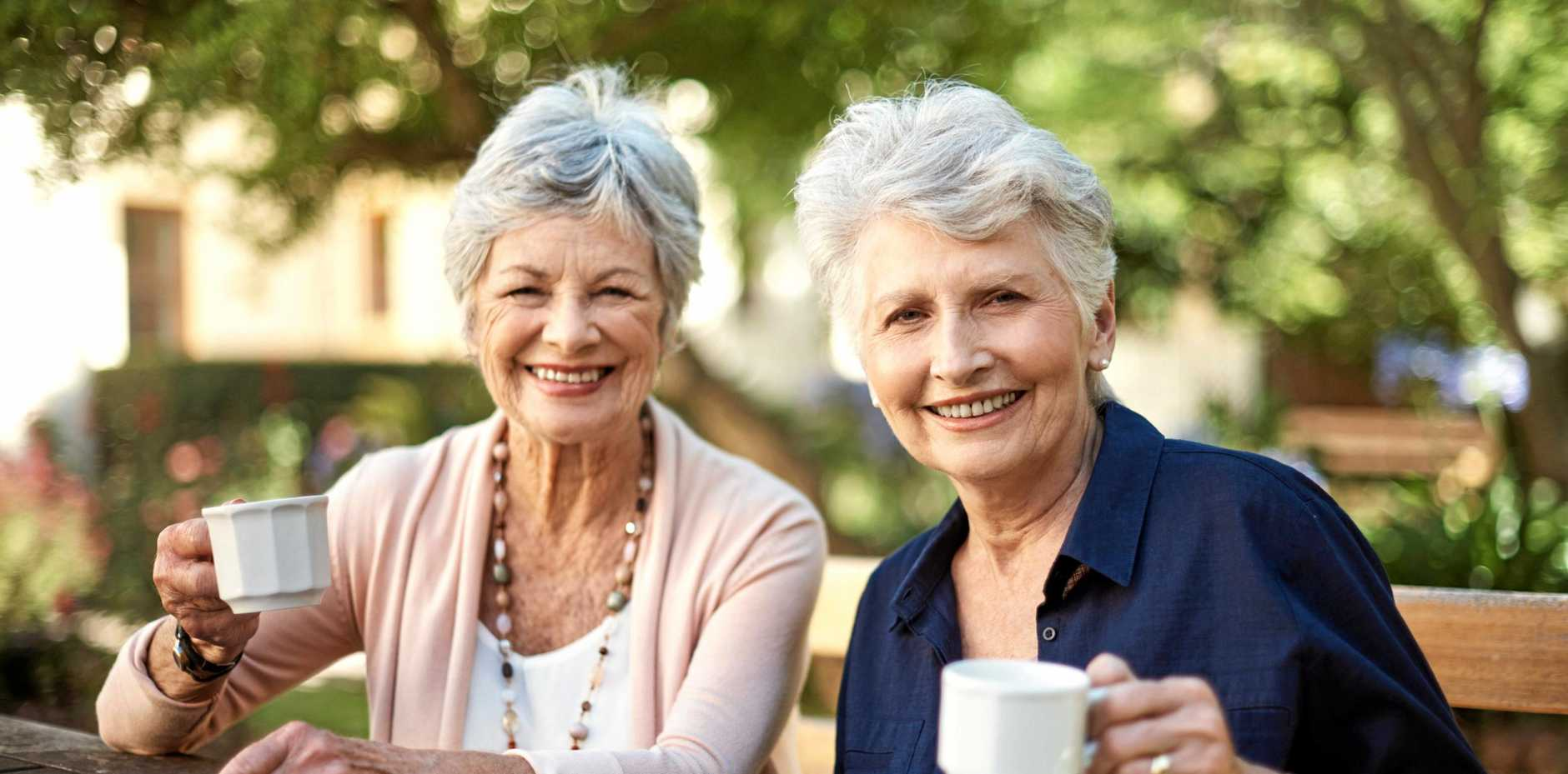 Portrait of two happy senior women having tea together out in the garden