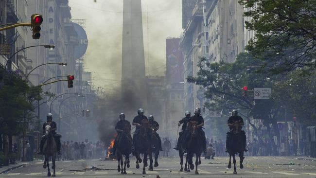 Mounted police charge anti-government demonstrators during 2001 protests in Buenos Aires, Argentina, after the South American nation defaulted on more than $US100 billion in foreign debt, banks were shuttered and the economy collapsed. Picture: Walter Astrada/AP