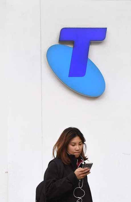 A woman looks at her phone as she walks past a Telstra store on Melbourne's central business district yesterday. Picture: William West