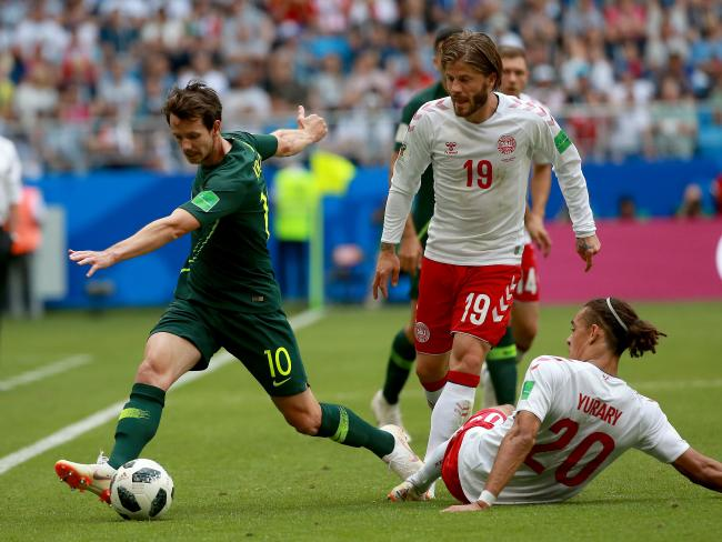 Robbie Kruse controls the ball against Denmark defenders. Picture: Toby Zerna