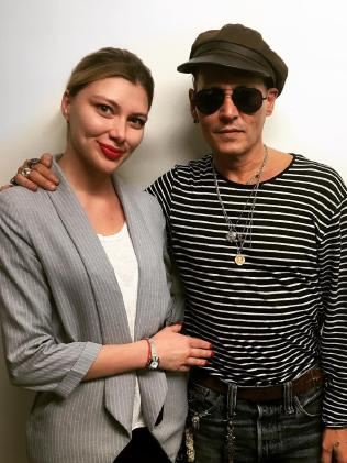 A skinny Depp poses with a fan.