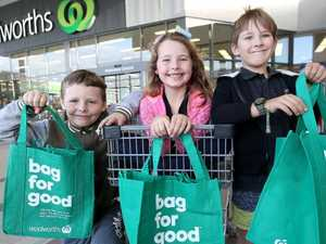 Siblings Cooper and Savannah Edgar and Kody Vaneck with green bags at Waterford, Thursday, June 21, 2018. From July 1 Woolworths will ban plastic bags. (AAP Image/Jono Searle)
