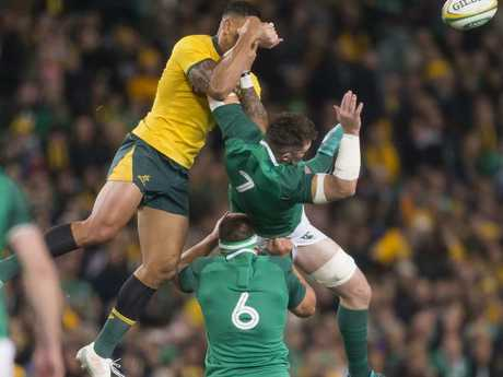 Ireland's Peter O'Mahony is headedd for the turf as Israel Folau flies high. Picture: Craig Golding/AAP
