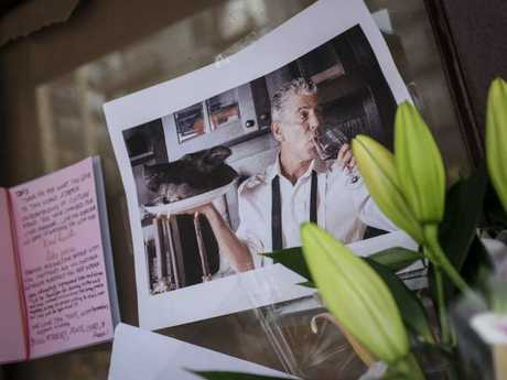 Notes, photographs and flowers are left in memory of Anthony Bourdain at the closed location of Brasserie Les Halles, where Bourdain used to work as the executive chef. Image: AFP