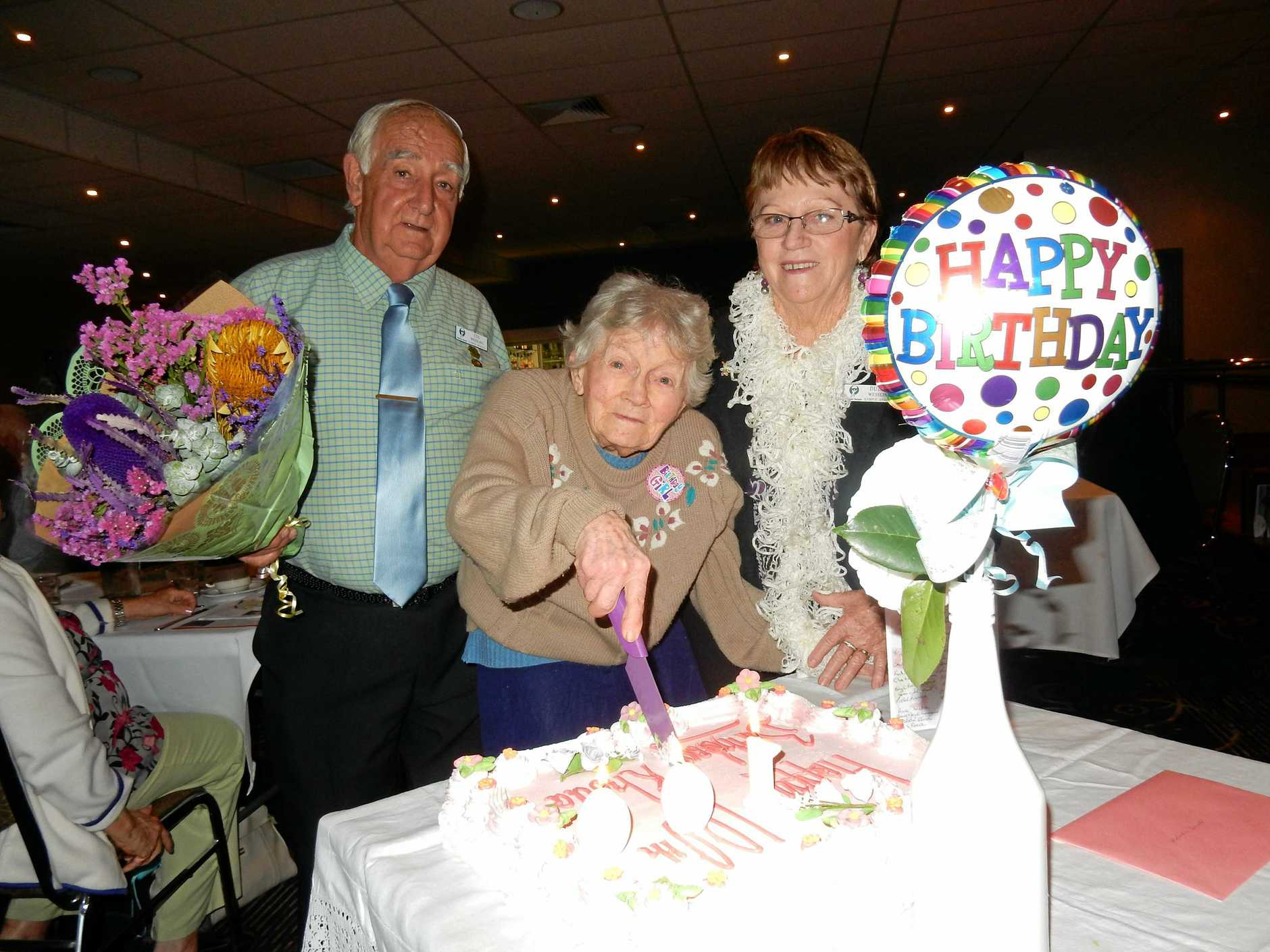 GYMPIE NATIONAL SENIORS. CENTENARIAN: Rhoda Small cuts her birthday cake with Gympie National Seniors president Col Wessling and his wife Dulcie.  Photo Contributed