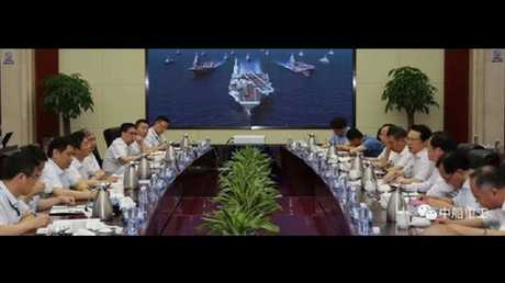 Senior China Shipbuilding Industry Corporation (CSIC) executives attend a function in the company's boardroom, with what appears to be a computer-generated rendering of a new aircraft carrier in the background.