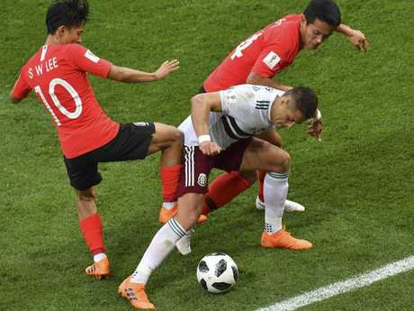 Mexico's Javier Hernandez takes on South Korea's Lee Seung-woo (L) and Oh Ban-suk.