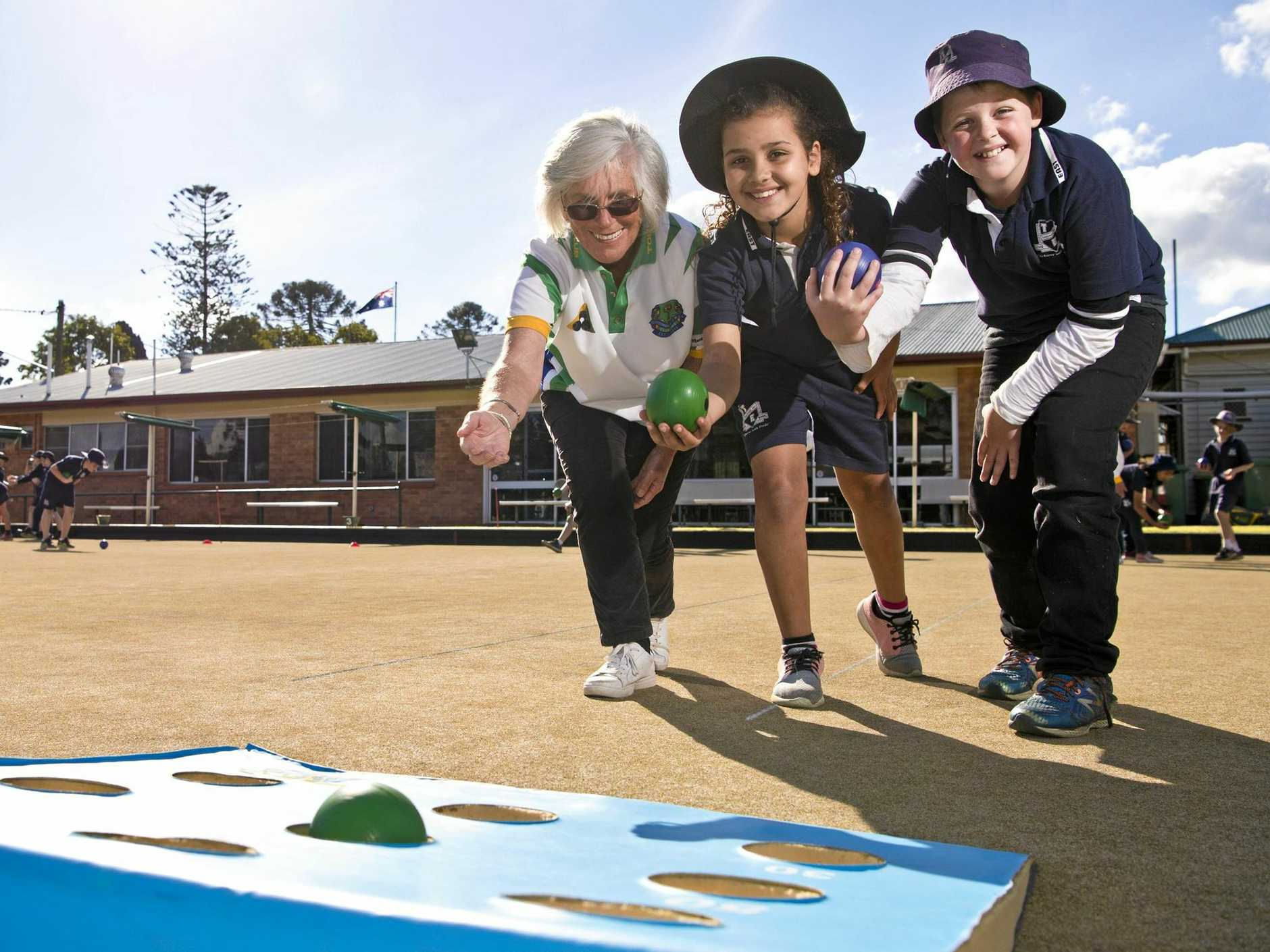 Toowoomba Bowls Club member Christine Plater (left) teaches Toowoomba East State School students Marianna De Paula and Luke Jordan the finer points of lawn bowls, Monday, June 25, 2018.