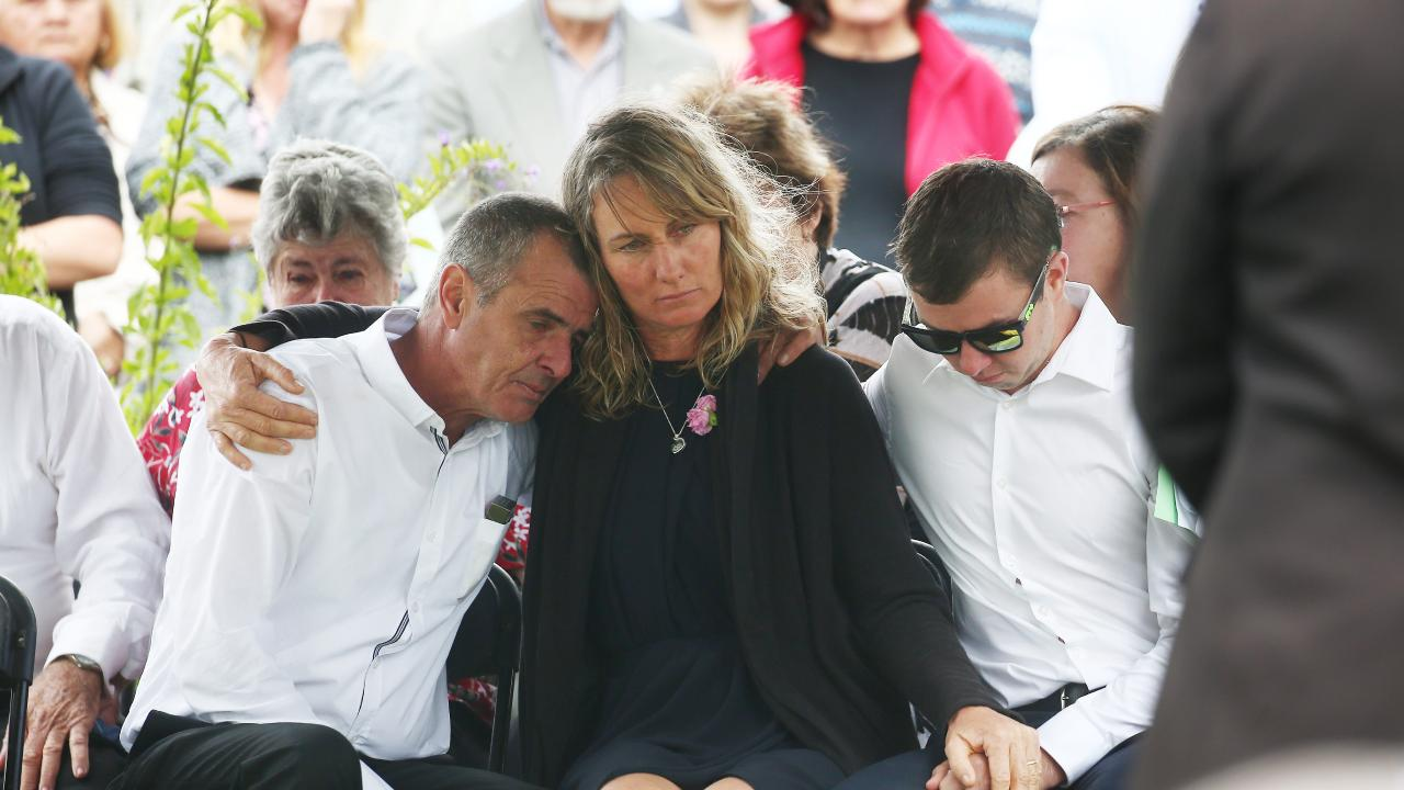 Scott Bowden, Rachael Bowden and Mark Bowden comfort each other at the funeral of their son and brother Michael Bowden, who died earlier this month at Weipa. PICTURE: BRENDAN RADKE