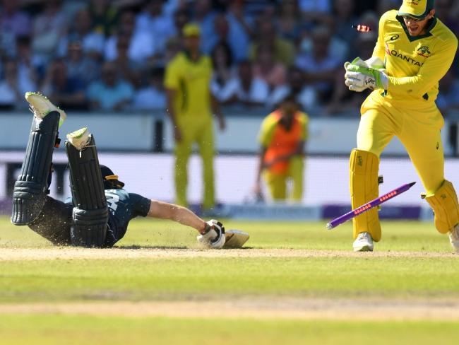 England's Jos Buttler (L) makes the crease as Australia's captain Tim Paine stumps the wicket during the fifth ODI cricket match between England and Australia at Old Trafford.