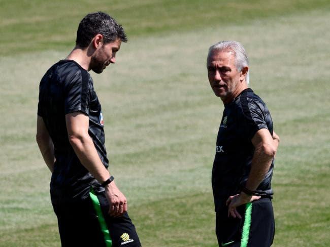 Australia's coach Bert van Marwijk (R) talks to assistant coach Mark van Bommel ahead of the Peru clash. Pic: AFP