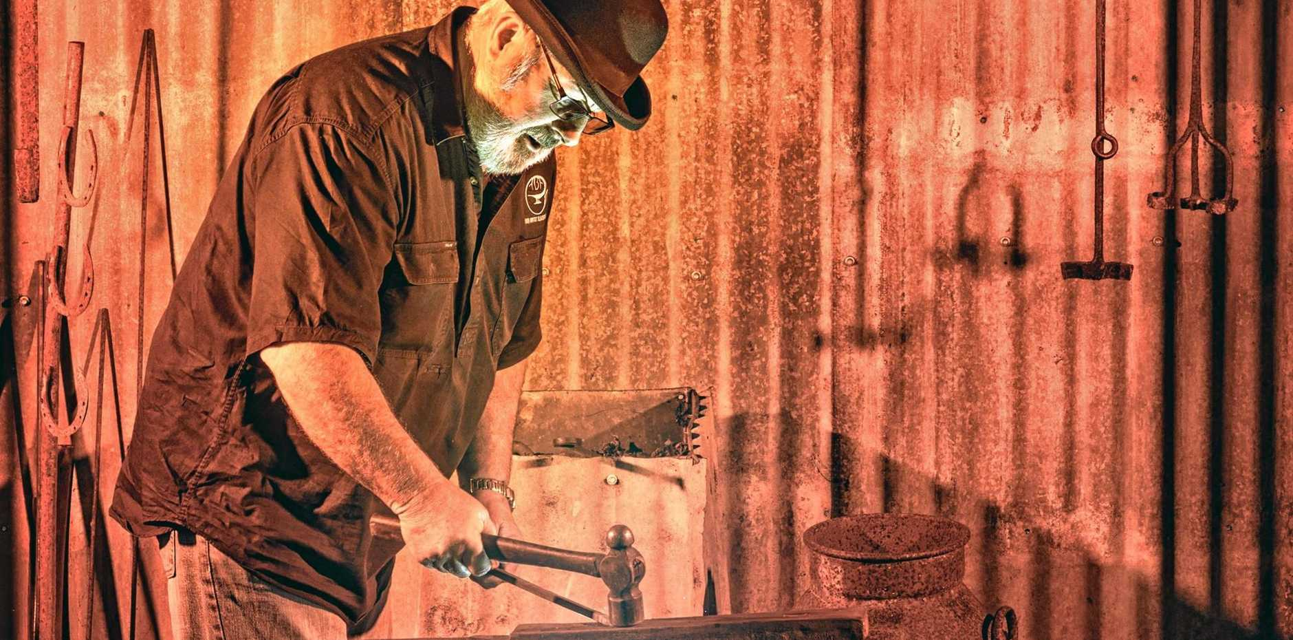 IRON MAN: Larry Adams plies his trade in the blacksmith's shed at the Lawrence Museum.