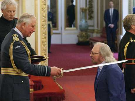Barry Gibb is knighted by  Prince Charles at Buckingham Palace.