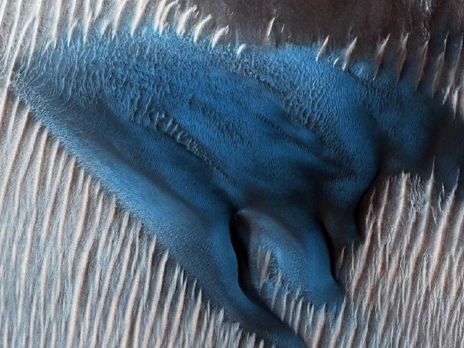 NASA's Mars Reconnaissance Orbiter's (MRO) camera zoomed in on the floor of the planet's Lyot Crater to capture this bright blue sand dune. Picture: NASA