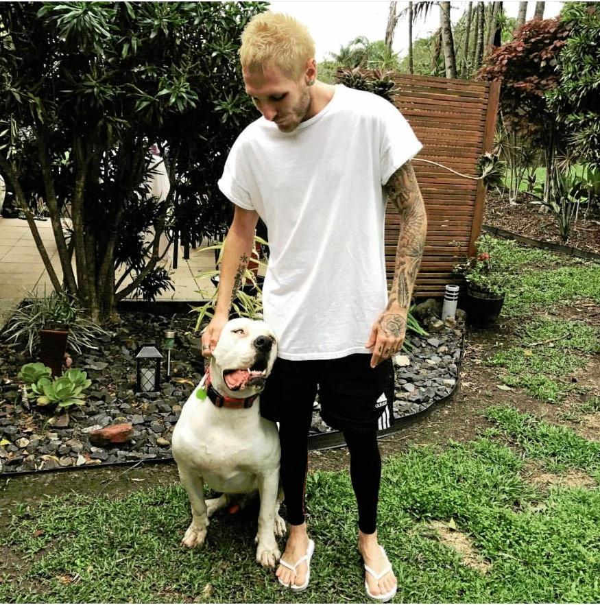 SAD GOODBYE: Josh Stewart, 25 was devastated when his American bulldog died suddenly after eating discarded fish at the Noosa River.