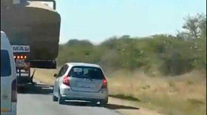 A silver car can be seen driving impatiently behind an oversized truck before attempting to overtake it.