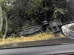 Truck rolls, stuck in embankment on Bruce Highway