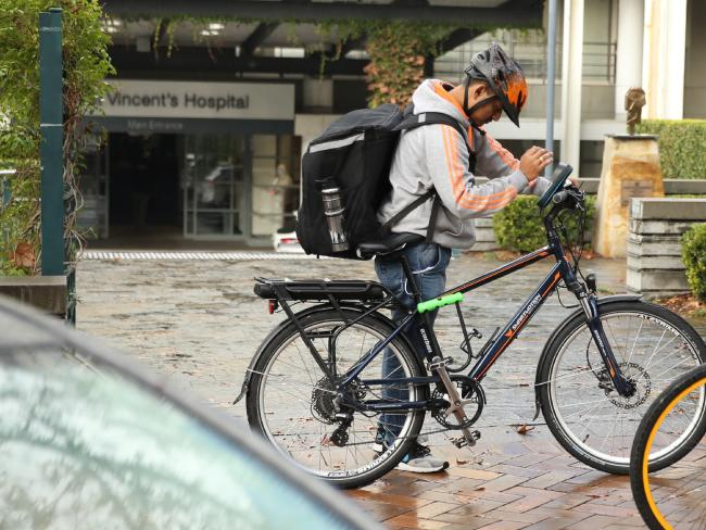 A delivery rider outside St Vincent's Hospital. Picture: John Grainger