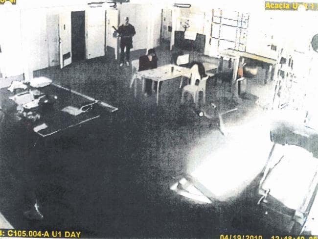 Enhanced CCTV image of Matthew Johnson behind Carl Williams before bludgeoning him to death.