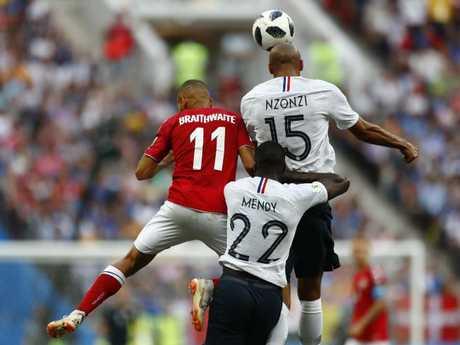 Denmark's Martin Braithwaite, left leaps for the ball with France's Steven Nzonzi. Pic: AP