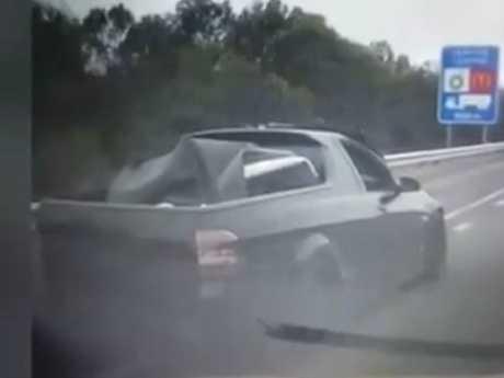 The black ute speeds down a Brisbane highway.