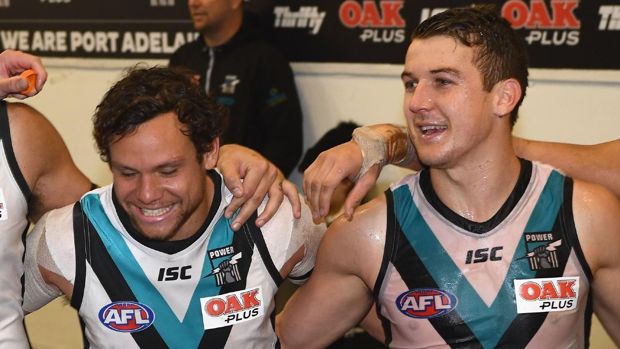 Port Adelaide's Steven Motlop and Jack Trengove sing the club song.