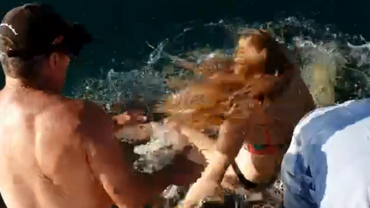 Shocking footage shows the moment this young woman was dragged into the water by a tawny nurse shark.