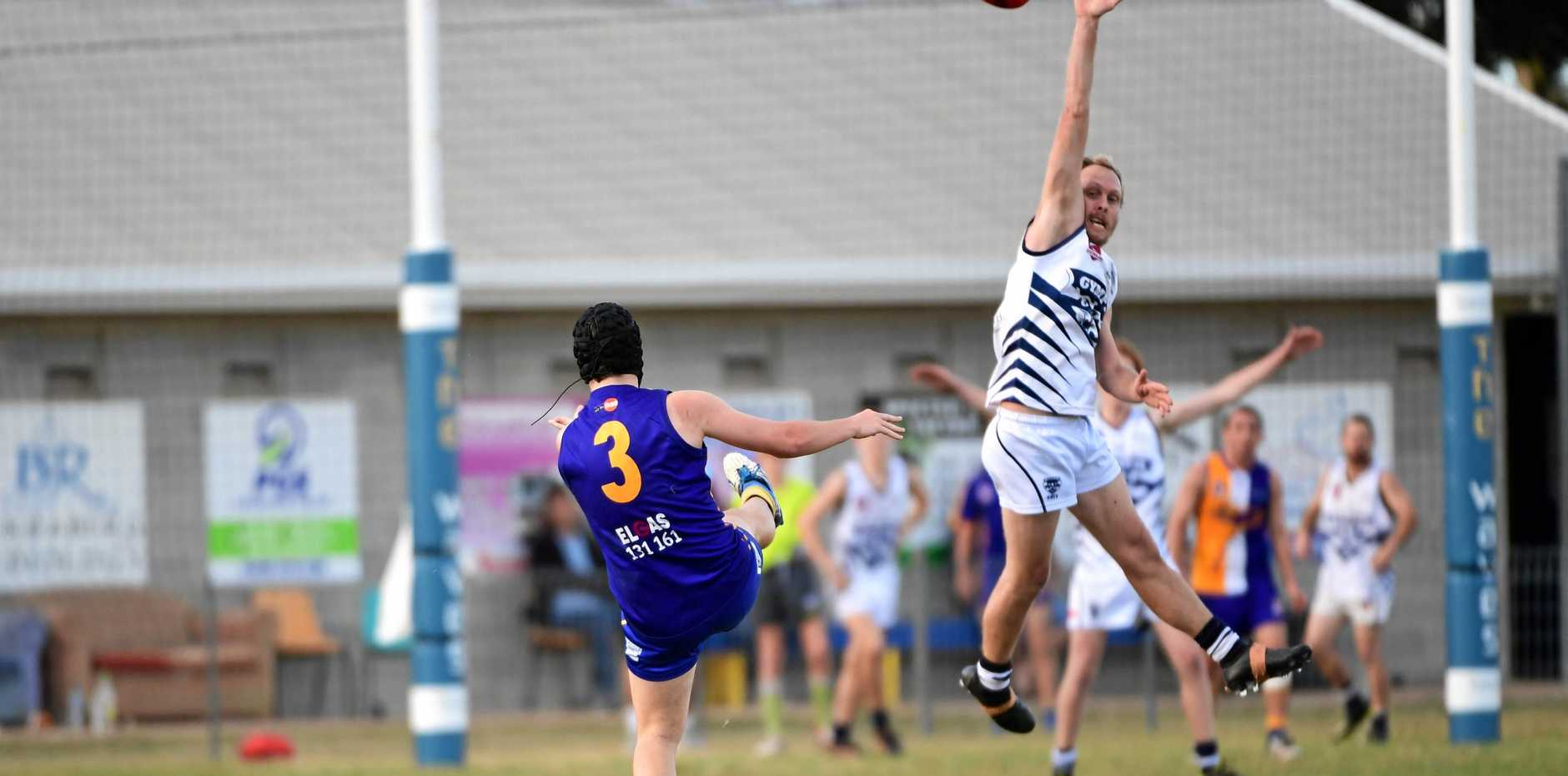 ALL RISE: The Waves' Damon Wood takes a shot for goal as the Cats defender attempts to stop the ball at Frank Coulthard Oval on Saturday.