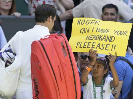 A fan holds a banner next to Roger Federer of Switzerland, asking for his headband, at the end of his Men's Singles first round match against Serbia's Dusan Lajovic. Picture: AP Photo
