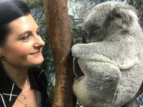 Professor Rebecca Johnson, meets a sleeping koala at Featherdale Wildlife Park in Sydney.