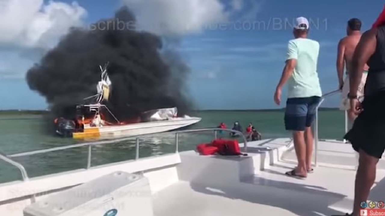The small, white boat is completely ablaze, with plumes of black smoke filling the air.