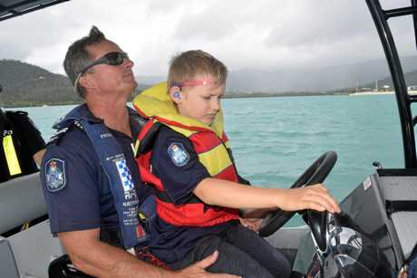 Connor Howse helping Senior Constable Adrian Fitzpatrick to drive the police patrol boat.