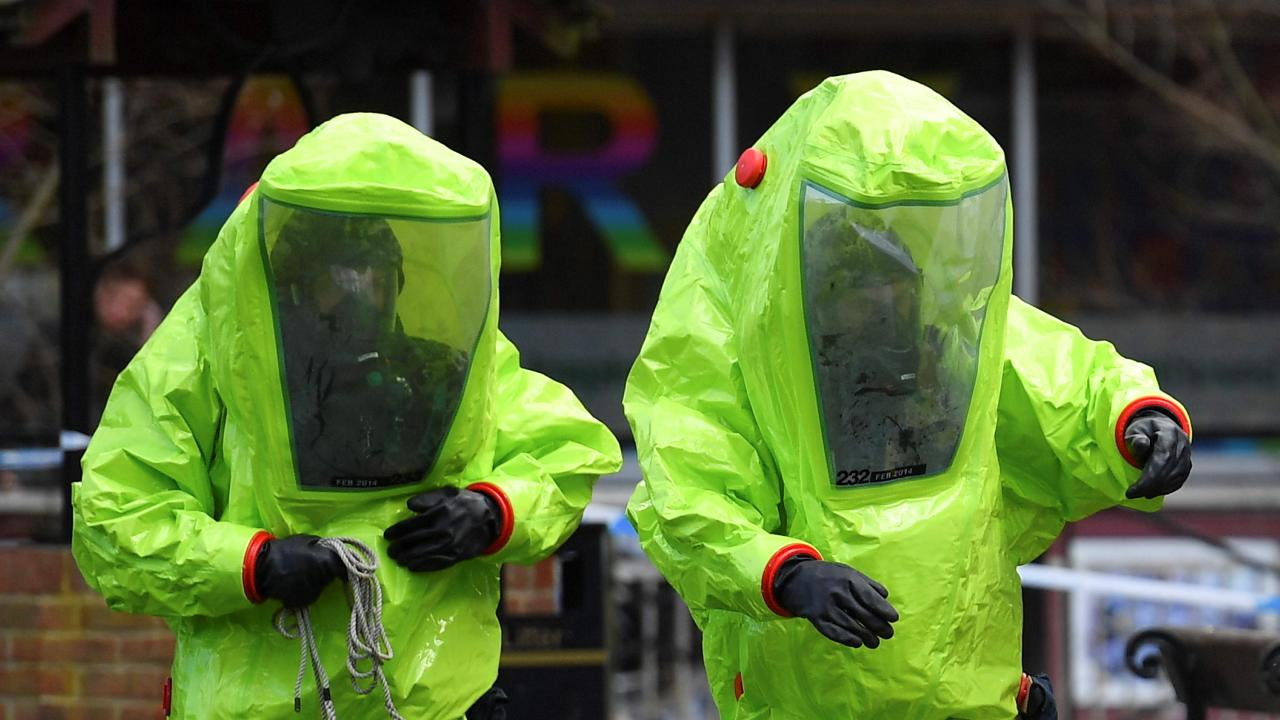Members of the emergency services in green biohazard encapsulated suits work to afix the tent over the bench where former Russian spy Sergei Skripal and his daughter Yulia were found on March 4 in critical condition at The Maltings shopping centre in Salisbury, southern England. Picture: AFP