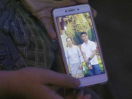 The aunt of coach Ekapol Chantawong shows a picture of the 25-year-old and his grandmother.