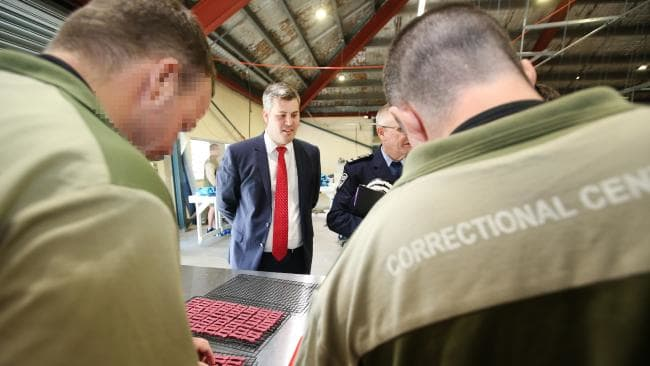 Minister Mark Ryan talks to inmates making dog biscuits at Borallon Correctional Centre. (Pic: Jono Searle/AAP)