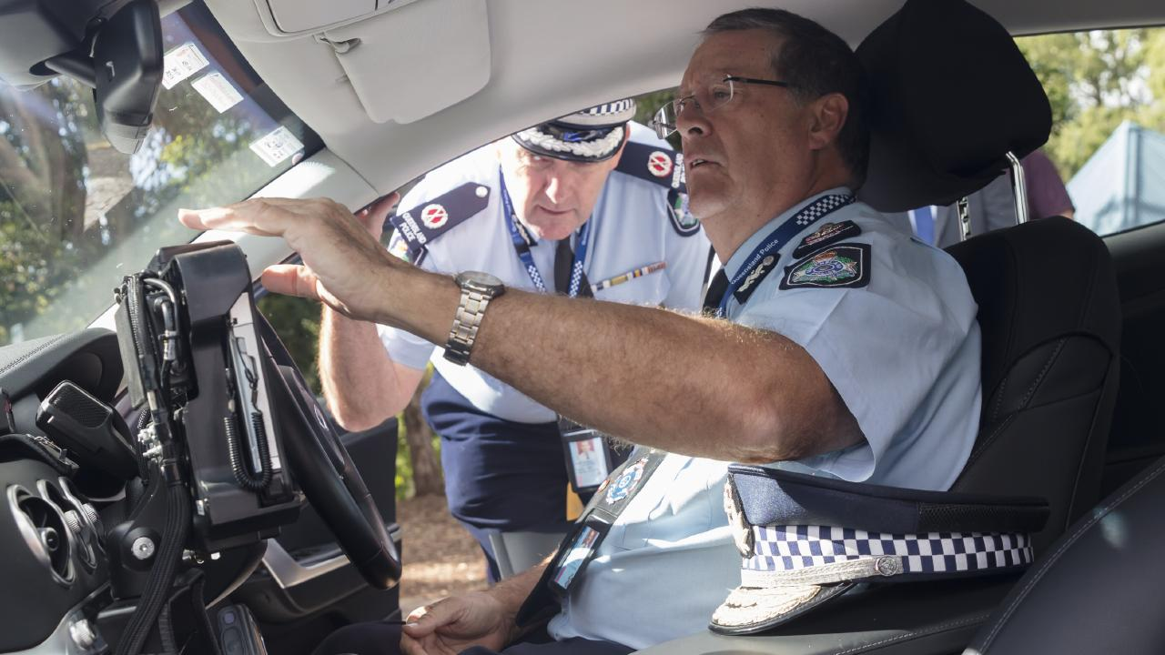 Queensland Police Commissioner Ian Stewart sits inside the new Kia Stinger highway patrol car as Assistant Commissioner (Road Policing Command) Mike Keating looks on. Picture: Supplied.