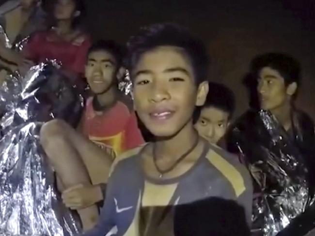 The boys smile as a Thai Navy SEAL medic helps them after they were found trapped in a cave. Picture: Royal Thai Navy Facebook Page via AP, File