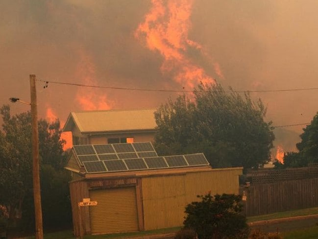 Flames engulf homes and yards in Tathra in march. Picture: Twitter /Jessie Collins