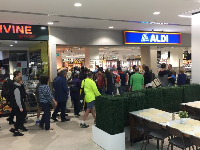 People rush in to the store as the doors open.