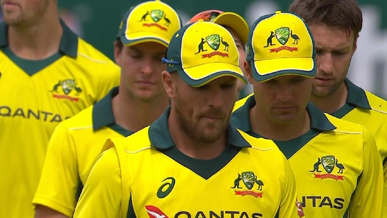 A dejected Aaron Finch leads Australia off.