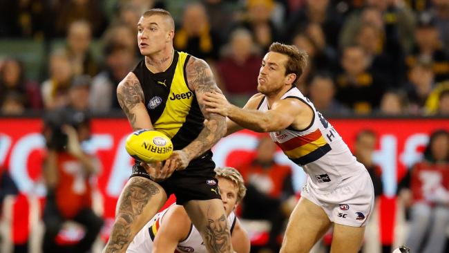 Dustin Martin of the Tigers handballs against Richard Douglas of the Crows. Picture: Michael Willson/AFL Media/Getty Images