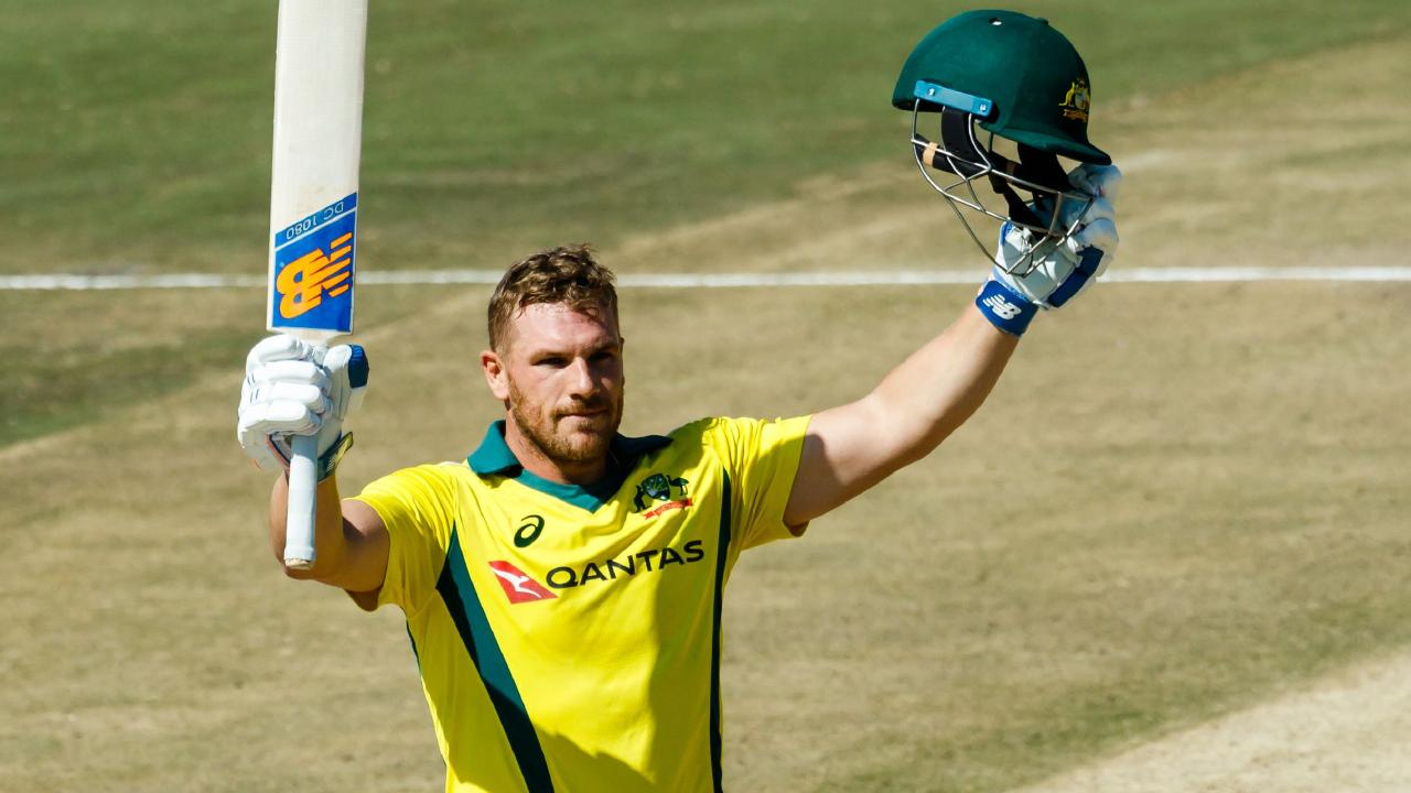 Aaron Finch raises his bat on reaching his century against Zimbabwe. Picture: AFP