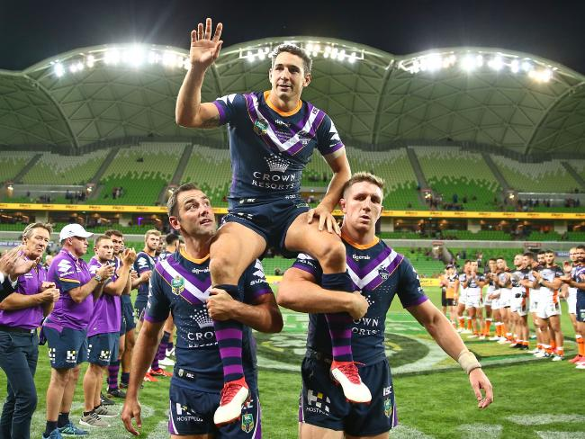 Cam Smith and Ryan Hoffman chair Billy Slater off the field. Picture: Getty