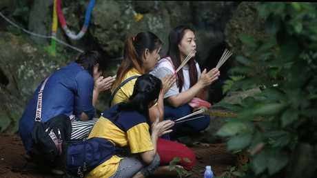 Family members pray near a cave where 12 boys and their soccer coach have been trapped since June 23, in Mae Sai, Chiang Rai. Picture: AP